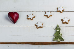 Christmas background with red heart green tree star shaped gingerbread cookies and cinnamon rolls on wood Royalty Free Stock Image