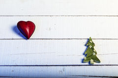 Christmas background with red heart and green tree on wood Stock Photography