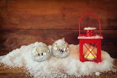 Christmas background with red lantern, bauble and snow over wooden background. Royalty Free Stock Photo