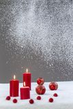 Christmas background red lit candle with a blowing snow over on grey background royalty free stock images
