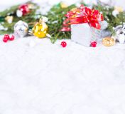 Christmas background with a red ornament, golden gift box, berries and fir in snow. Stylish mock up for branding Royalty Free Stock Photography