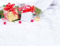 Christmas background with a red ornament, golden gift box, berries and fir in snow. Stylish mock up for branding Royalty Free Stock Photo