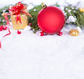 Christmas background with a red ornament, golden gift box, berries and fir in snow. Stylish mock up for branding Stock Image