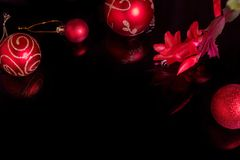 Christmas background with a red ornament and ribbon on a black background. Christmas background with a red ornament, Red Christmas ball and Blooming red stock images