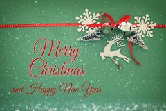 Christmas background with red silk traditional ribbon, white deer, evergreen tree, paper snowflakes and jingle bells. Stock Photos
