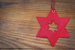 Christmas background, red star of felt hanging over old wood Stock Images
