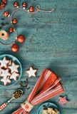 Christmas background in red and white on rustic turquoise wood. Top view on Christmas cookies, spices and decorations. Toned image, text space Stock Image