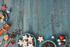 Christmas background in red and white on rustic turquoise wood. Top view on Christmas cookies, spices and decorations. Toned image, text space Royalty Free Stock Photography