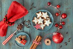 Christmas background in red and white on rustic turquoise wood. Top view on Christmas cookies, spices and decorations Stock Photos