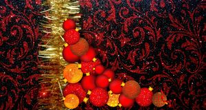 Christmas background with red and yellow ornament on a black glitter textured background. stock photo