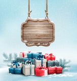 Christmas background with a retro wooden sign and gift boxes. Royalty Free Stock Image