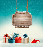 Christmas background with a retro wooden sign and gift boxes. Royalty Free Stock Images