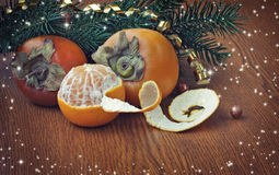 Christmas background with ripe persimmons and tangerine Royalty Free Stock Image