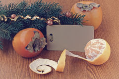 Christmas background with ripe persimmons and tangerine Royalty Free Stock Photo