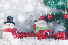 Christmas background with santa claus and snowman. On the snow with red christmas ball hanging in fir tree with copy space, vintage style Royalty Free Stock Photo