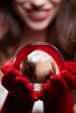 Christmas background with a shiny glass ball on model hands. Chr Royalty Free Stock Photo