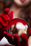 Christmas background with a shiny glass ball on model hands. Chr Stock Photos