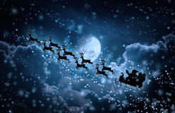 Christmas Background. Silhouette Of Santa Claus Flying On A Sleigh Pulled By Reindeer. Stock Photography