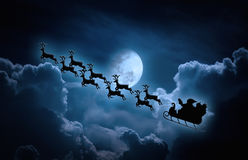 Free Christmas Background. Silhouette Of Santa Claus Flying On A Sleigh Pulled By Reindeer. Royalty Free Stock Images - 93422189