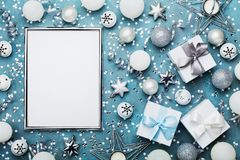 Christmas background. Silver frame with xmas decoration, gift box, confetti and sequins on vintage blue table top view. Flat lay. Royalty Free Stock Images