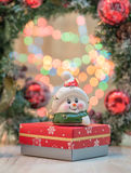 Christmas background. Small toy on top of a Christmas present box .In the background a Christmas Tree ornament and blurry colore Royalty Free Stock Photos