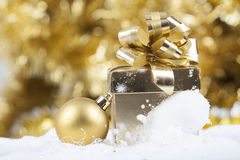 Christmas background with snow, Christmas ball and gift box Stock Images