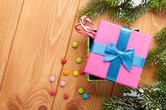 Christmas background with snow fir tree, gift box and candies Stock Photos