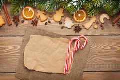 Christmas background with snow fir tree, spices, gingerbread coo Stock Images