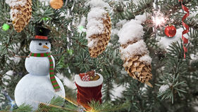 Christmas background : a Snowman and a bag of gifts. Snowman and bag with gifts on the background of decorated Christmas tree with cones Royalty Free Stock Photo