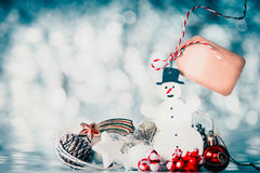 Christmas background with snowman, festive decoration and blank tag with place for text at winter bokeh background. Front view Stock Image