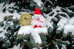 Christmas background. Snowman and golden ball on the tree branches Stock Image