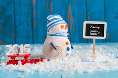 Christmas background with Snowman and red sled. Stand With word 2016 near direction sign Xmas. Postcard Royalty Free Stock Images