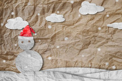 Christmas Background, Snowman wearing red Santa hat in winter with white clouds snow, paper cut made of crumpled paper Royalty Free Stock Image