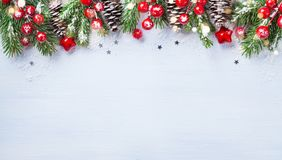 Christmas background with snowy fir branches, cones and bokeh lights. Holiday banner or card