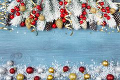 Christmas background with snowy fir tree and colorful holiday balls on blue wooden table top view. Greeting card with space