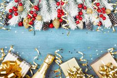 Christmas background with snowy fir tree, gift box, champagne and holiday decorations on blue wooden table top view. Greeting card. With space for text stock images