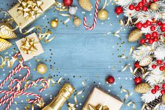 Christmas background with snowy fir tree, gift or present box, champagne and holiday decorations on blue wooden table top view. Greeting card with space for royalty free stock images