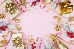 Christmas background with snowy fir tree, gift or present box, champagne and holiday decorations on pink table top view. Flat lay. Christmas background with royalty free stock photos