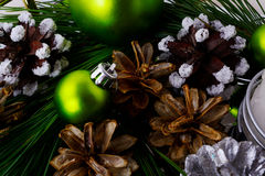 Christmas background with snowy pinecone and green ornaments Royalty Free Stock Image