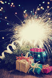 Christmas background with sparkler and gifts Stock Photos