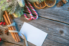 Christmas background with spices, popsickes, needles and card on wooden table, traditional christmas greeting card Stock Photos