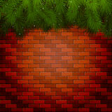 Christmas background with spruce branches on a brick wall Royalty Free Stock Photos