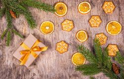 Christmas background with spruce branches, gift box, orange slices and homemade biscuits in the form of snowflakes. Royalty Free Stock Image