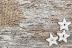 Christmas background with star shapes and burlap textile. On the old wood background royalty free stock image