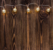 Christmas background with string lights. vintage garland on wooden planks. Stock Photo