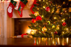 Christmas background of table against Christmas tree and firepla
