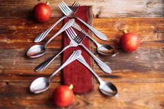 Abstract christmas tree made from cutlery on a dark slate,grey stone or concrete background.Top view with copy space. Stock Image