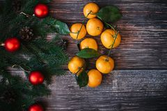 Christmas background with tangerines, fir branches, red balls. Traditional festive winter decor for the new year stock photo