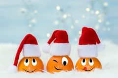Christmas background with tangerines in Santa Claus hat. Funny characters from the original idea of the concept Stock Photography