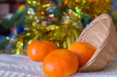 Christmas background, tangerines in a wicker basket. Christmas background, Christmas lights, tangerines in a wicker basket stock image